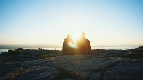 Two People Sitting on the Beach in Silhouette