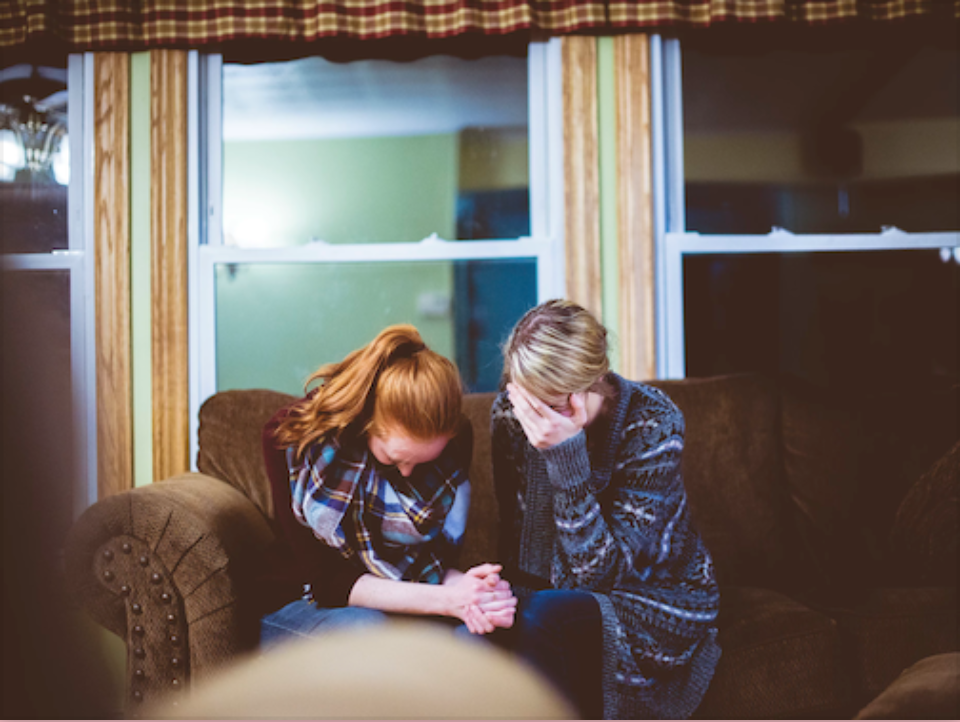 Two women bowing their heads in prayer with hands held